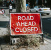 Road ahead closed sign on the sidewalk